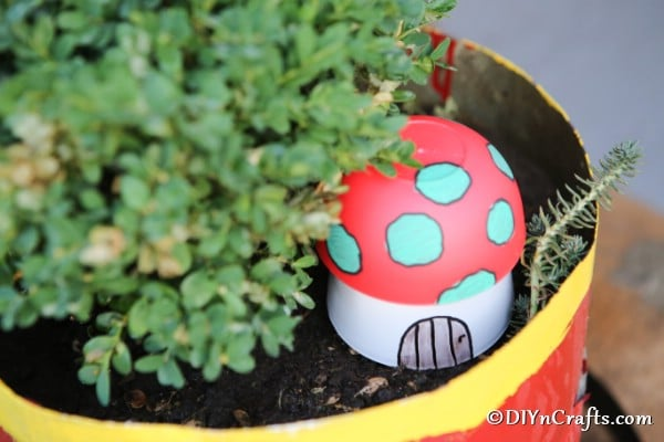 A painted mushroom garden decor in a planter with flowers