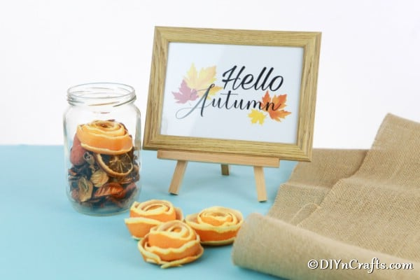 Orange flowers being displayed on a blue surface with a hello autumn sign in the background