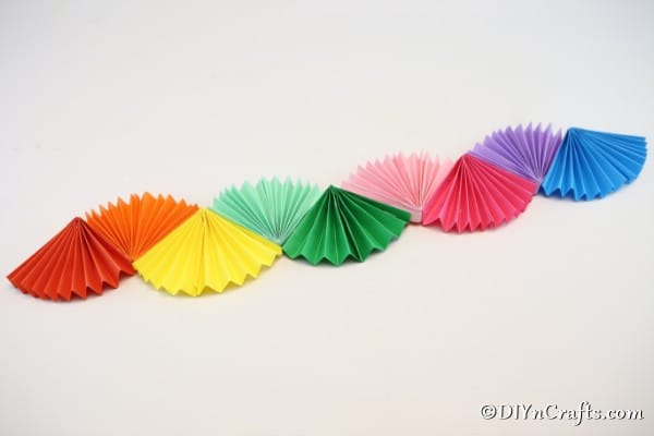 A complete rainbow paper fan party decoration on a white wall