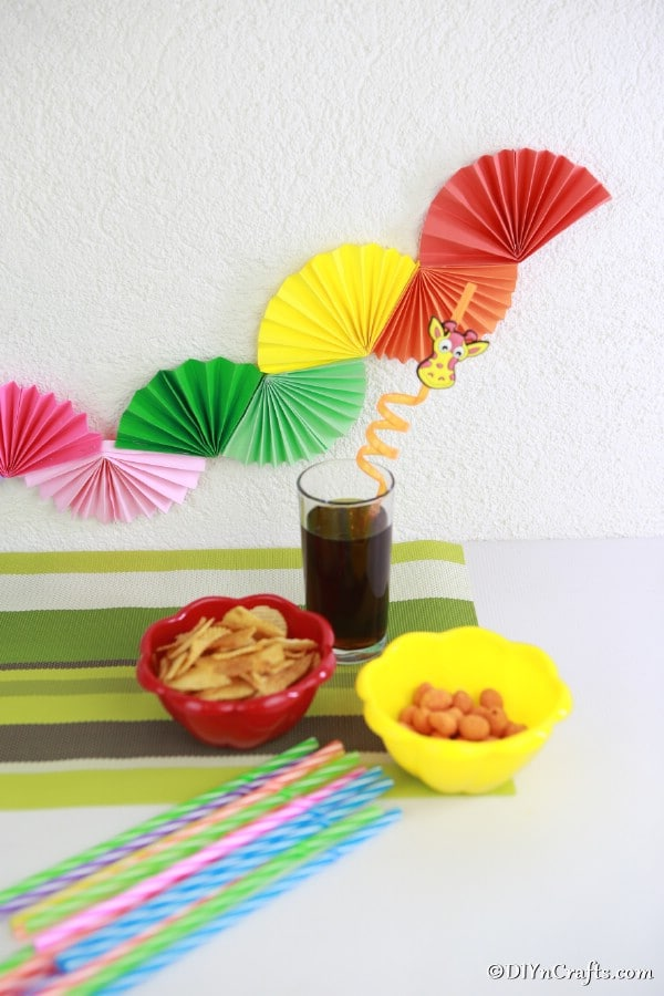 Simple paper fan party garland hanging behind a buffet table