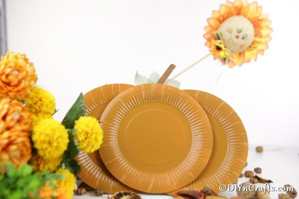 Paper plate pumpkin displayed with other flowers and fall decor