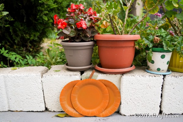 Paper plate pumpkin craft leaning against a block wall outside