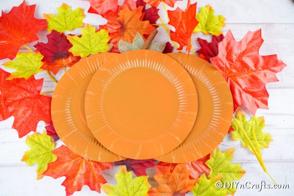 Paper plate pumpkins on a surface with leaves in the background