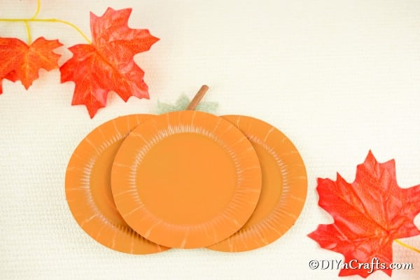 A completed paper pumpkin plate craft laying on a white surface
