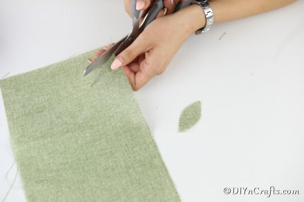 Cutting leaves out of green fabric to attach to the paper plate pumpkin craft