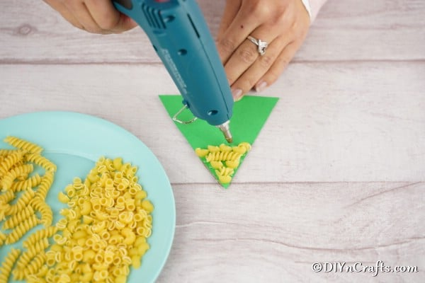 Gluing pasta to the cardboard Christmas decoration craft