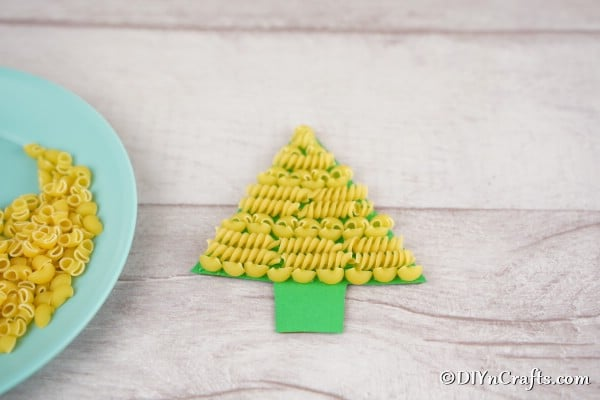 Gluing pasta to a christmas tree craft