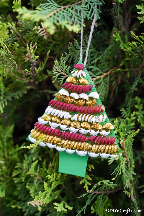 A pasta tree christmas decoration hanging on a green holiday tree