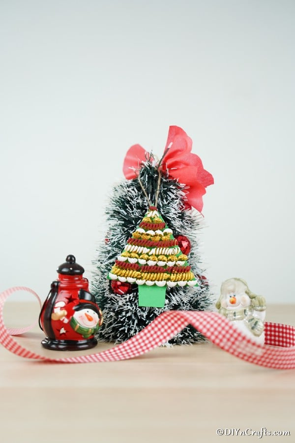 A small tree with a pasta Christmas tree decoration hanging on the front with red ribbon