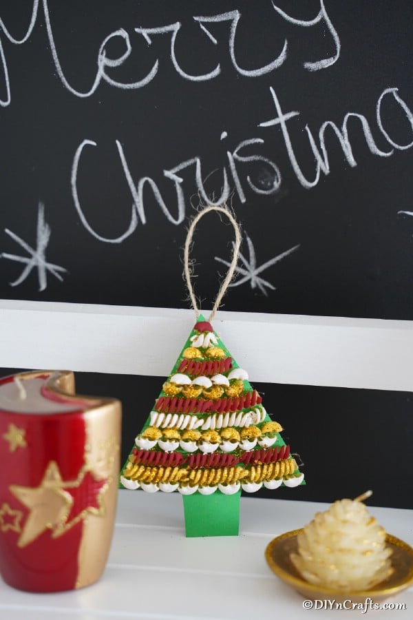 A pasta Christmas tree decoration leaned against a chalkboard with other holiday decor