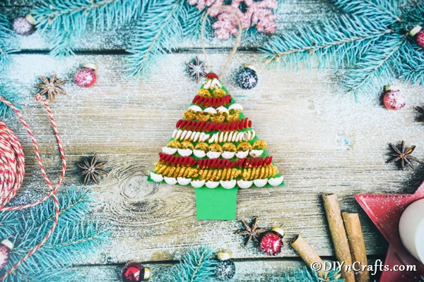 A completed pasta tree christmas decoration on a wooden table surrounded by blue garland