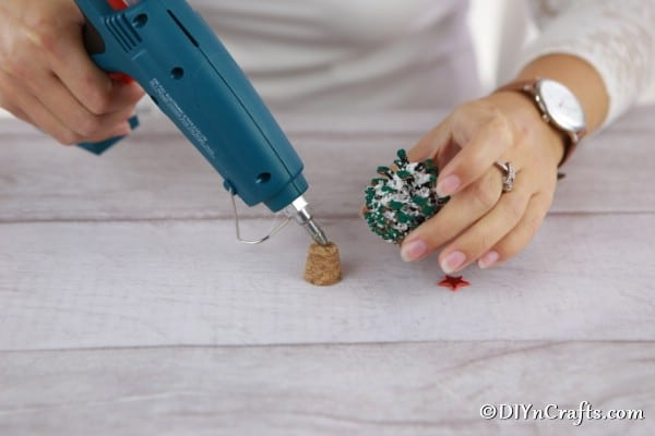 Gluing the pine cone ornament on top of a wine bottle cork