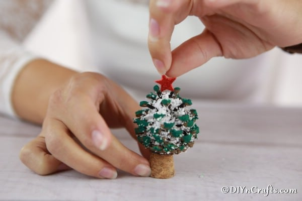 Adding the star to the top of a pine cone Christmas tree decoration