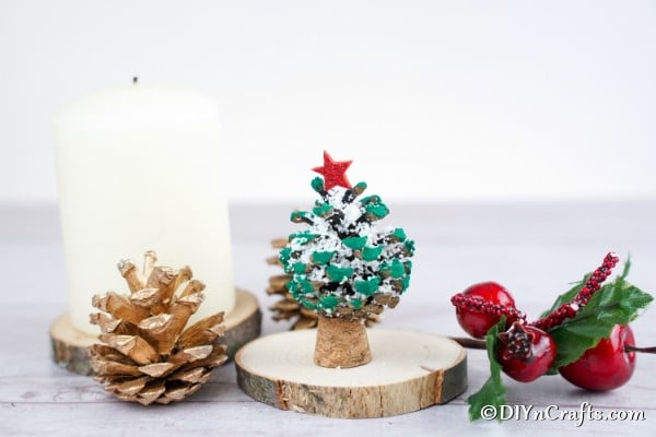 A completed pine cone ornament on a slice of wooden tree trunk
