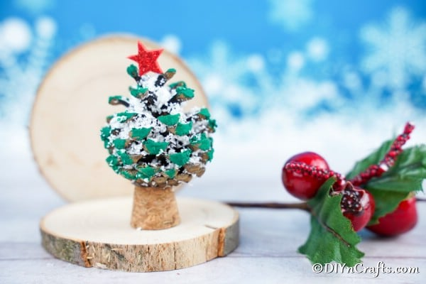 A small homemade pine cone ornament for Christmas on a table with a blue background