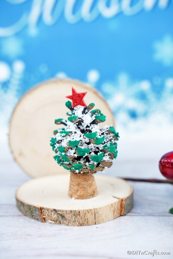A pine cone ornament on a small slice of wood with a blue backgruond