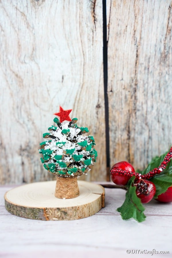 A miniature pine cone ornament sitting on a counter with other Christmas decorations