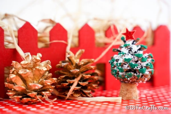 A mini pine cone Christmas tree ornament sitting on a red surface with red fence in background