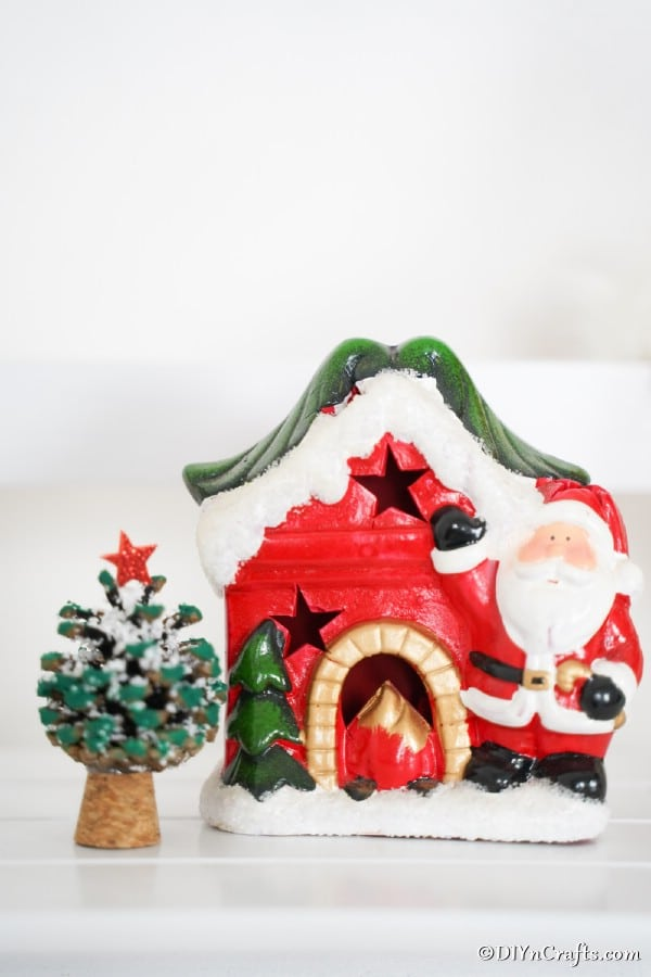 A holiday pine cone ornament tree sitting next to a santa house on a counter