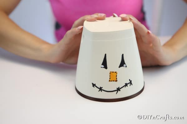 A clay pot with a DIY scarecrow face painted and ribbon added around the bottom