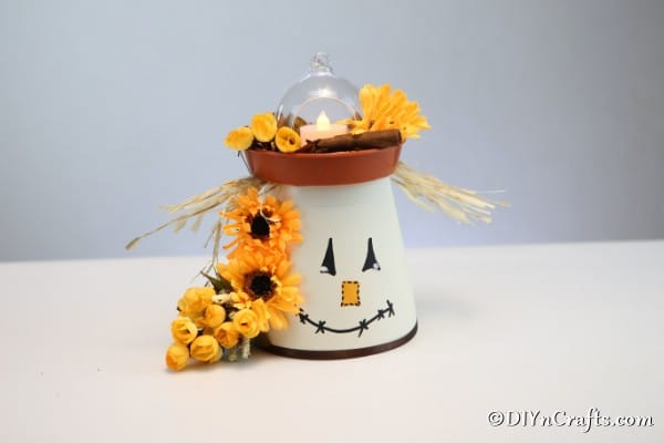 A completed DIY scarecrow clay pot lantern