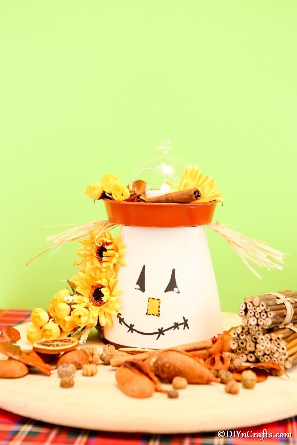 A clay pot lantern scarecrow sitting in front of a light green background