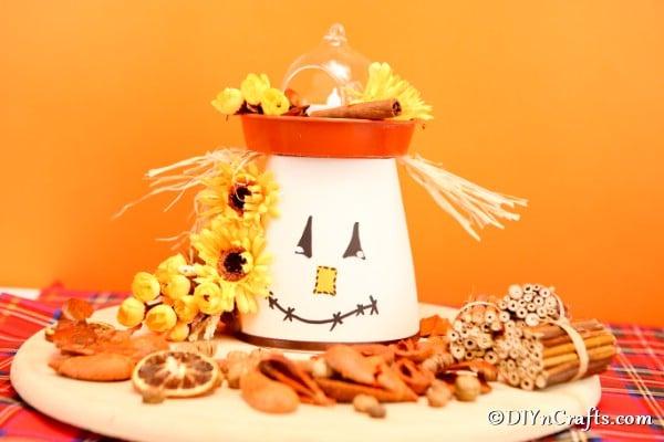 A diy scarecrow flower planter lantern in front of an orange background