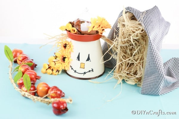 DIY Scarecrow clay pot lantern sitting on a blue counter with fall decorations around it