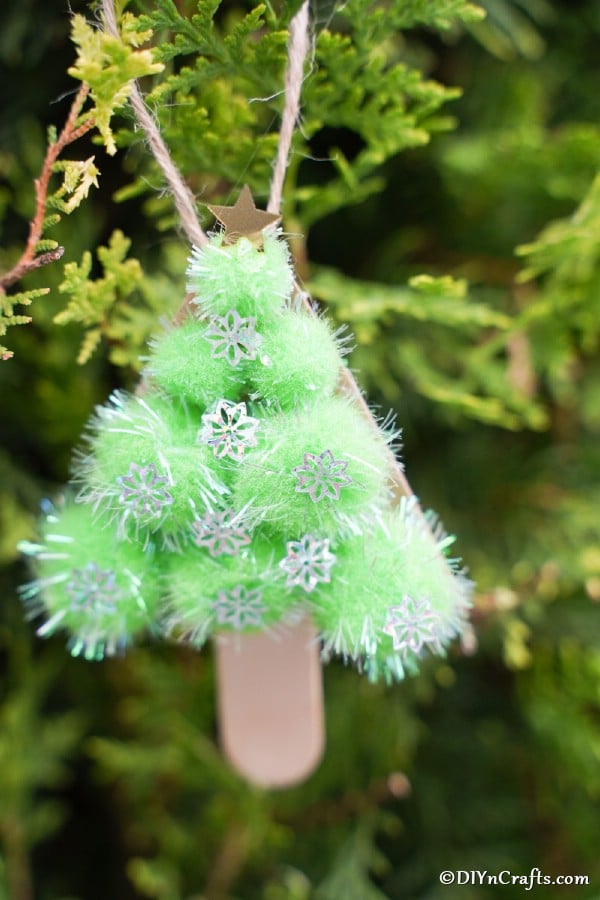 An up close picture of a completed pom pom Christmas tree hanging on a real tree