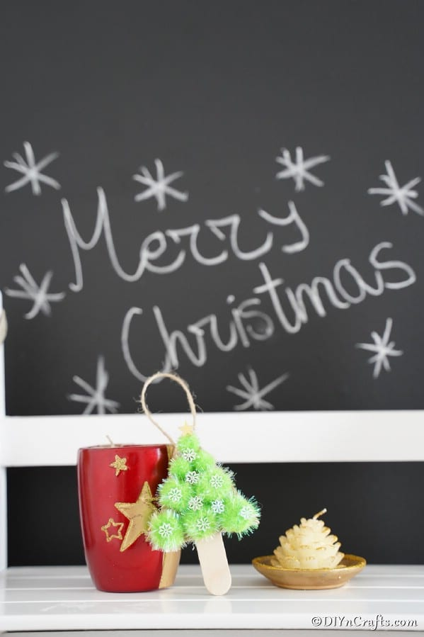 A Christmas ornament pom pom tree leaned up against a red mug in front of a chalkboard holiday announcement