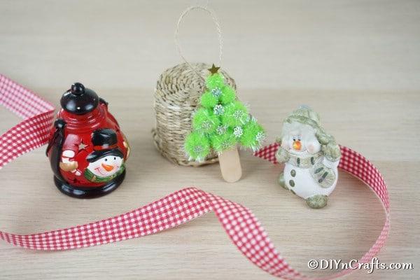 A pom pom tree for Christmas displayed on a table alongside other Christmas figurines