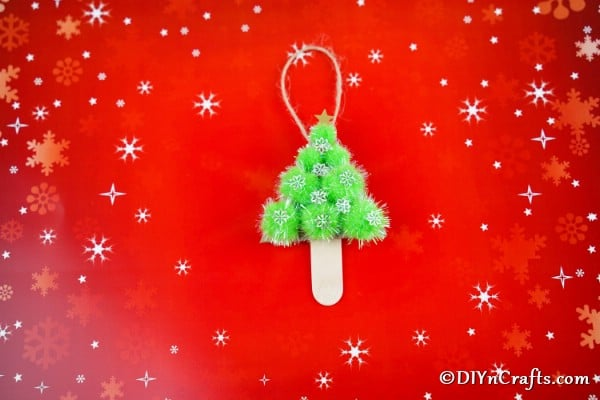 A decorative pom pom tree for Christmas laying on a red background