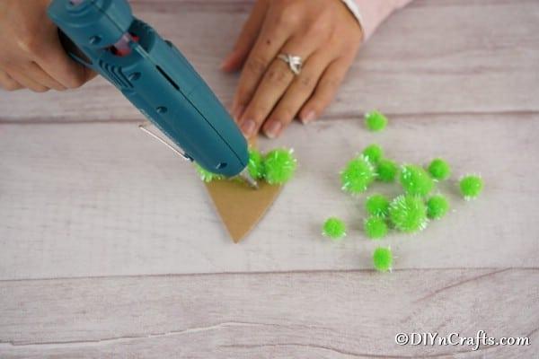 Gluing pom poms onto the Christmas tree craft