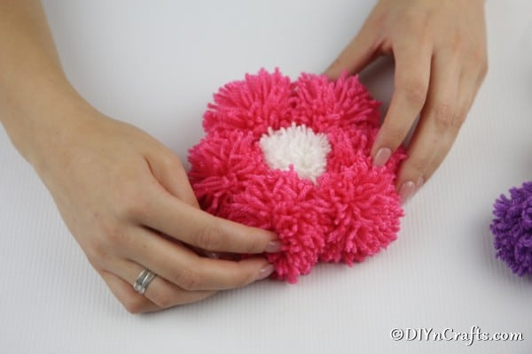 Securing yarn pom poms to cardboard to create a flower petal