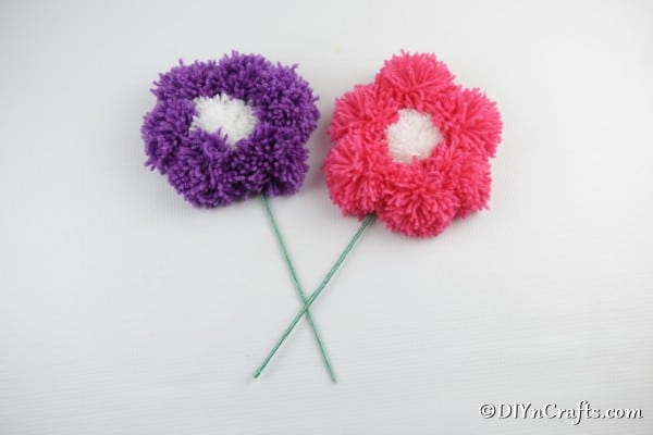 A purple and pink yarn pom pom flower sitting on a white surface