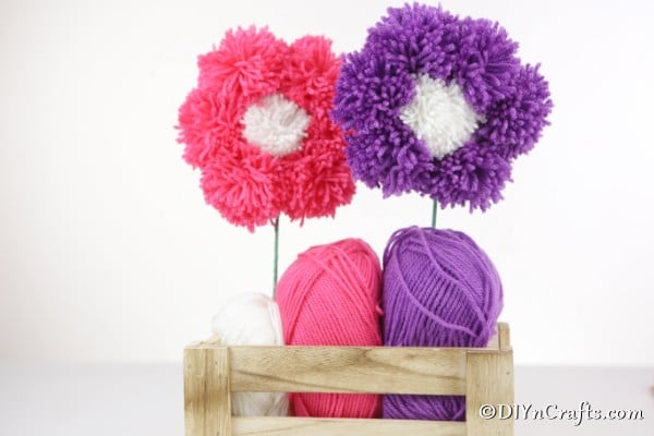 Pink and purple yarn pom poms flowers displayed in a wooden basket