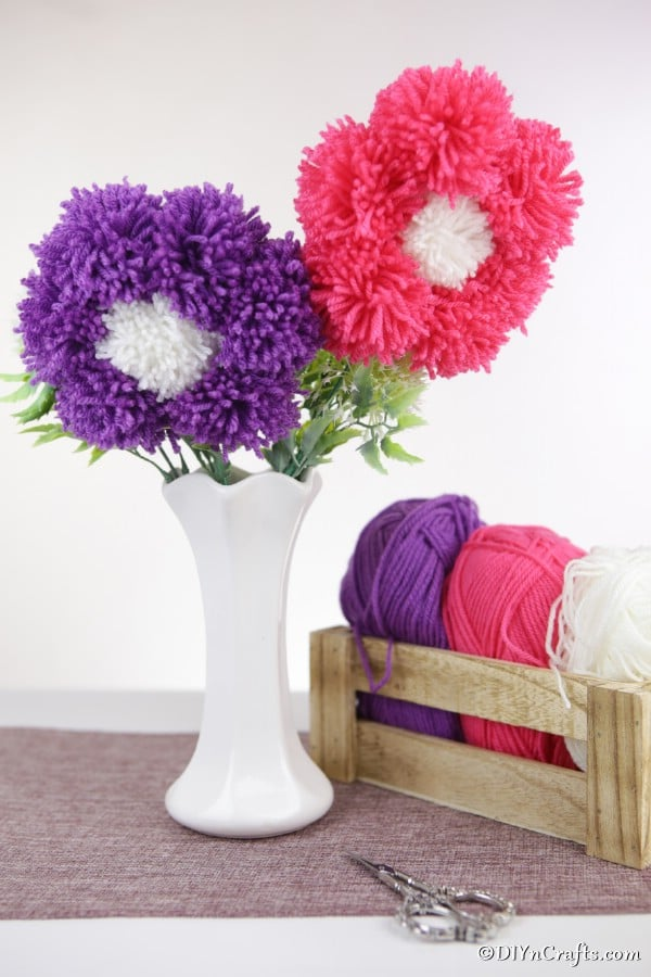 A pink and purple flower in a white face made from yarn pom poms