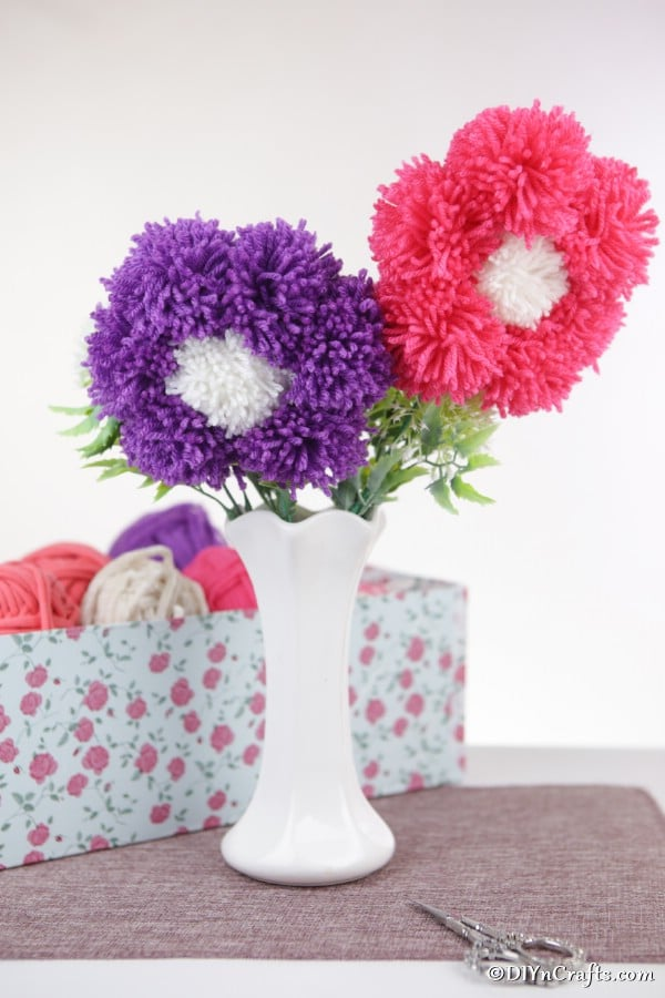 A white vase filled with pink and purple pom pom flowers