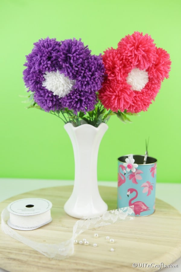 A white vase with yarn pom poms flowers and a green background