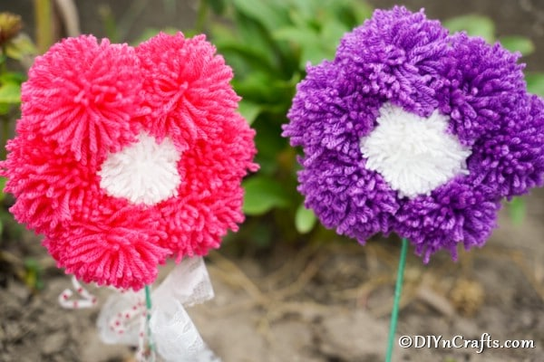 Pink and purple yarn pom poms flowers outside