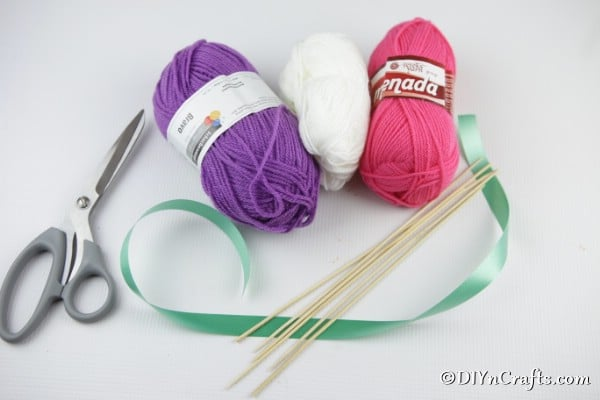Supplies needed to make yarn pom poms for a flower bouquet