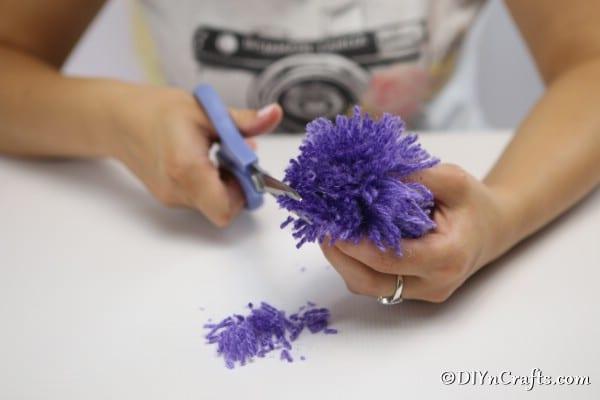 Cutting ends of yarn to create a flower look on yarn pom pom flowers