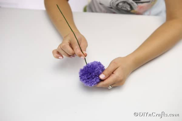 Attaching the wire stem to the yarn flowers