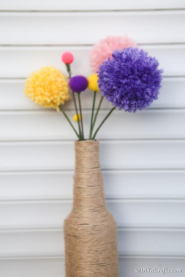 A twine wrapped vase filled with pom pom flowers in various colors