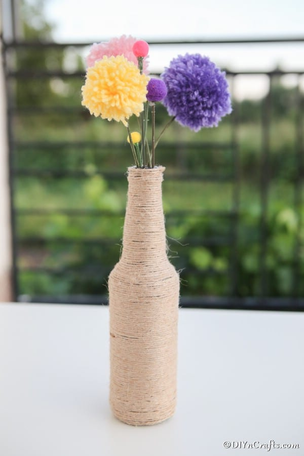 A rustic vase filled with yarn pom pom flowers