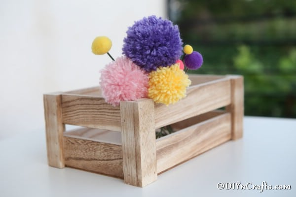 A wooden box on a counter with yarn pom pom flowers inside