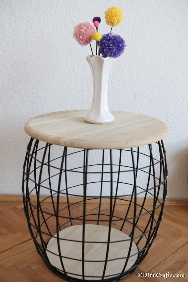 A vase filled with pom pom flowers on a small wooden and wire stool