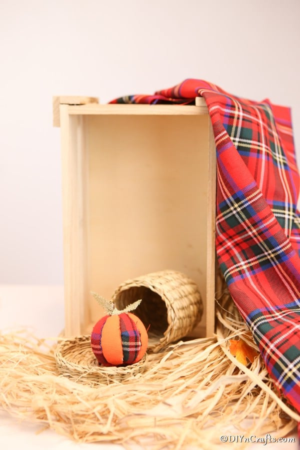A pumpkin ornament displayed sitting on hay inside a wooden box