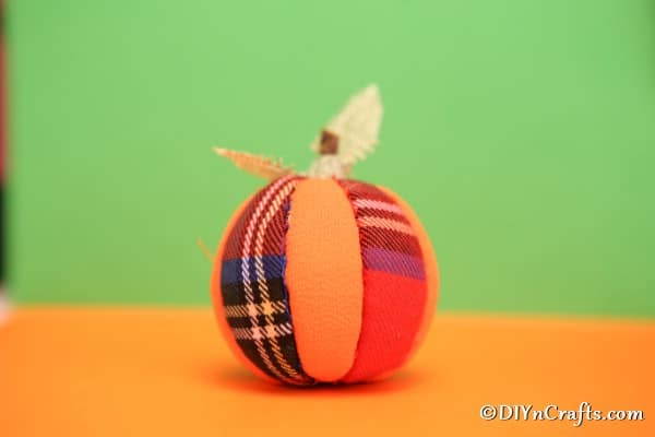 A pumpkin ornament sitting on an orange surface with green background