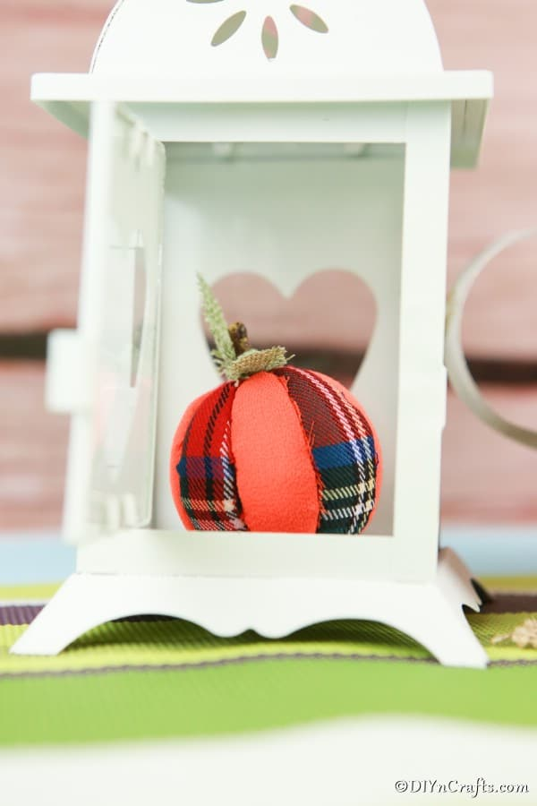 A cloth pumpkin ornament sitting inside a white lantern holder